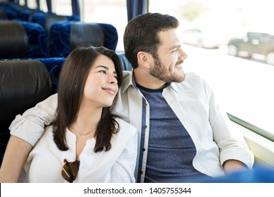 Smiling couple looking through window while traveling in bus