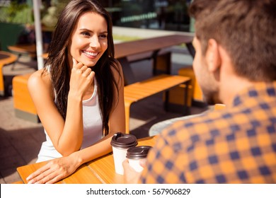 Smiling couple in love talking in outdoor cafe and drinking coffee.