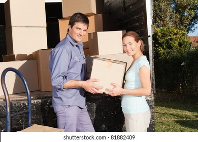 Smiling couple moving luggage at their new house