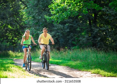 Smiling couple on bicycles in summer