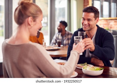 Smiling Couple On Date Making Toast Before Enjoying Pizza In Restaurant Together