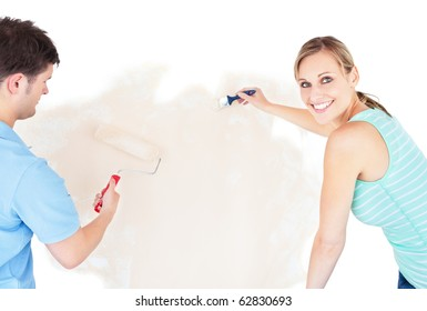 Smiling couple painting a room in their new house