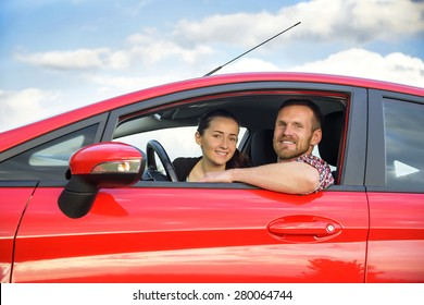 Smiling couple people in a red car
