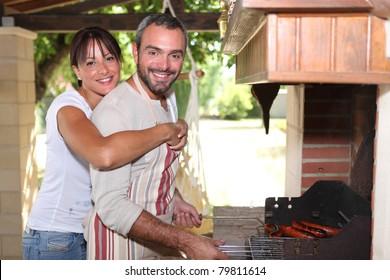 Smiling couple preparing barbecue