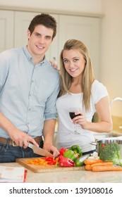 Smiling couple preparing dinner in kitchen