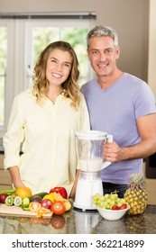 Smiling couple preparing healthy smoothie in the kitchen