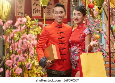 Smiling couple with presents standing among decorations for Chinese New Year