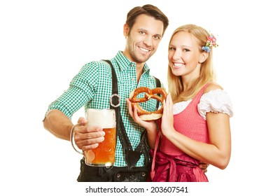 Smiling couple with pretzel and beer at Oktoberfest in Bavaria