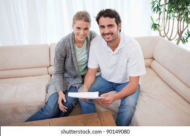 Smiling couple reading a letter in their living room