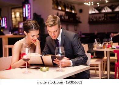 Smiling couple reading menu  and choosing meal