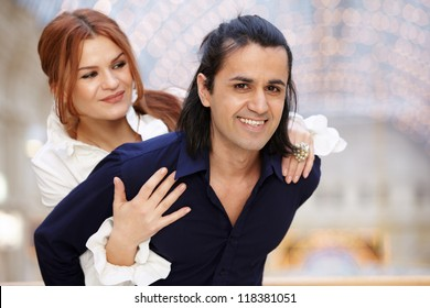 Smiling couple, she embrace him from behind
