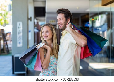 Smiling couple with shopping bags looking far away at shopping mall