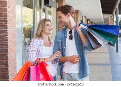 A smiling couple with shopping bags at the mall