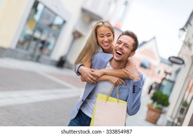 Smiling couple with shopping bags outdoors