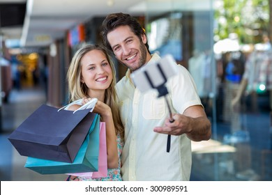 Smiling couple with shopping bags taking selfies with selfiestick at shopping mall