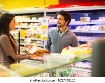 Smiling couple shopping at the grocery store