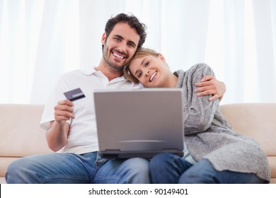 Smiling couple shopping online in their living room