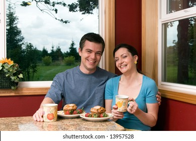 A smiling couple sitting by large windows having breakfast.  The man has his arm around the woman who is holding a coffee cup.