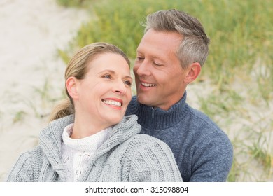 Smiling couple sitting on the sand at the beach