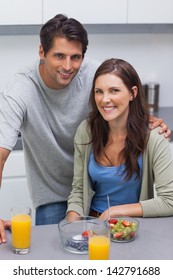 Smiling couple sitting in their kitchen