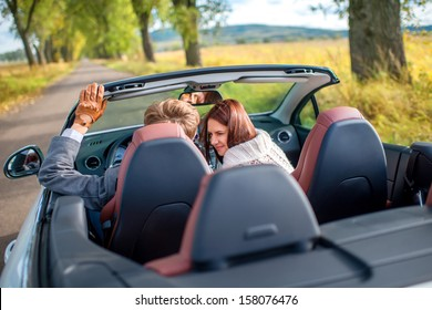 smiling couple sitting in their white car on the road