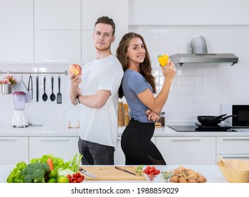 Smiling couple standing in kitchen while preparing healthy food.  Man holding red apple and woman holding yellow bell pepper.