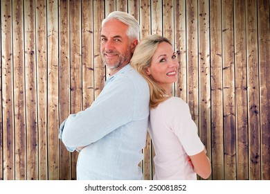 Smiling couple standing leaning backs together against wooden planks