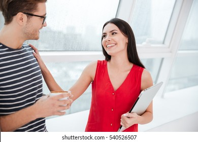 Smiling couple standing near the window in office. Woman holding laptop and touching shoulder of man which holding cup of coffee