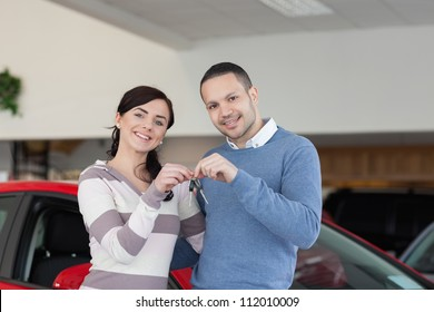 Smiling couple standing next to a car while holding keys