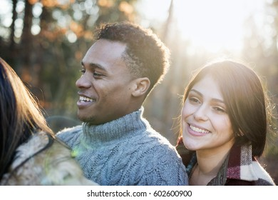 Smiling couple standing in a sunlit forest in autumn