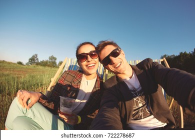 smiling couple in sun glasses makes selfie and sitting in a lounge chair at a picnic on a bright sunny day