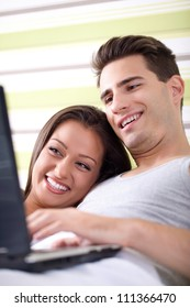 Smiling couple using a laptop lying on their bed at home