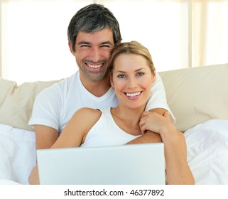Smiling couple using a laptop lying in the bed at home