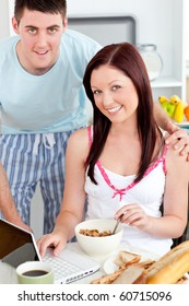 Smiling couple using a laptop while breakfast at home in the kitchen