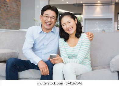 Smiling couple using smartphone on the sofa