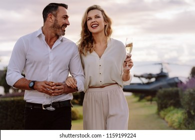 Smiling couple walking outdoors holding a glass of wine. Caucasian man and woman with a drinks walking together with a helicopter in background.