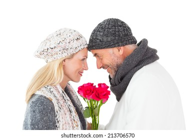 Smiling couple in winter fashion posing with roses on white background