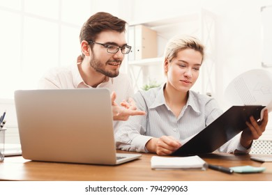 Smiling couple of young colleagues working in modern office. Two coworkers discussing their work, looking on documents, copy space