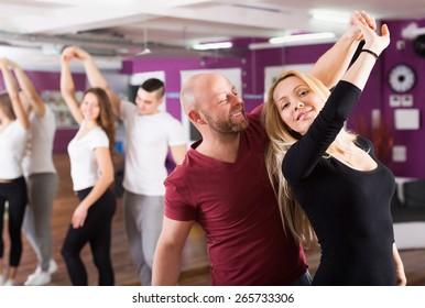 Smiling couples enjoying of partner dance indoor