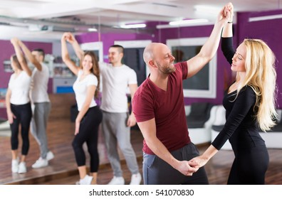 Smiling couples enjoying of partner dance