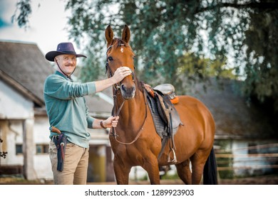 Smiling cowboy holding his brown horse