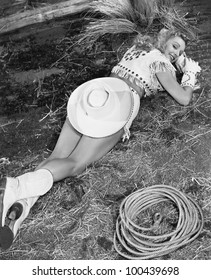 Smiling cowgirl lying on ground