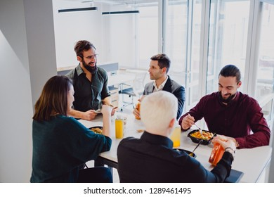 Smiling coworkers having lunch at the table in the office