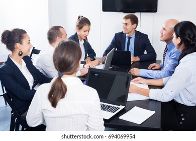Smiling coworkers meeting at conference room to discuss project in office