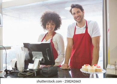 Smiling co-workers posing together behind the counter at the bakery