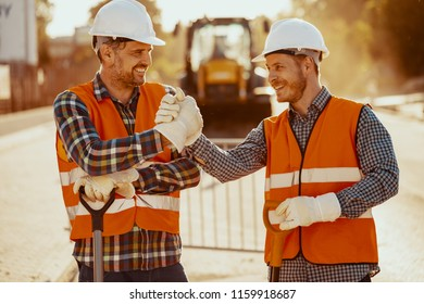 Smiling coworkers in reflective vests and white helmets after roadwork