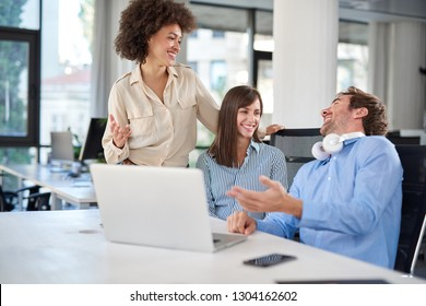 Smiling coworkers talking to each other in office. On table laptop. Start up business concept.
