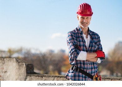 Smiling craftsman with arms folded looking at camera. Happy construction worker with tool kit on waist and work gloves standing on rooftop. Portrait of satisfied bricklayer with copy space.