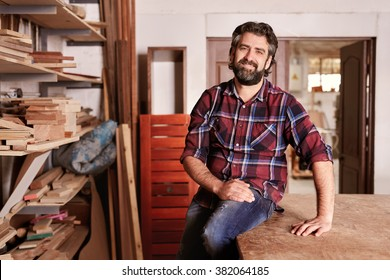 Smiling craftsman sitting in his woodwork studio for a portrait, with shelves of different  pieces of wood, where he works as a carpenter
