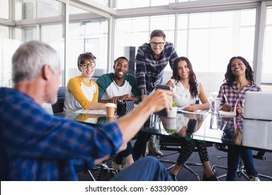 Smiling creative team looking at mobile phone held by businessman at office